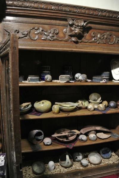 Vitrinedans laquelle sont présentés des objets en grès et porcelaine ainsi que des collier en perles baroques...