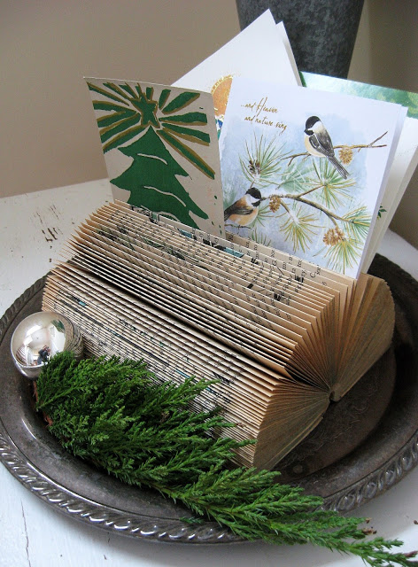 What-a-fun-idea-to-use-an-old-book-to-display-your-Christmas-cards-via-Four-Corners-Design.jpg